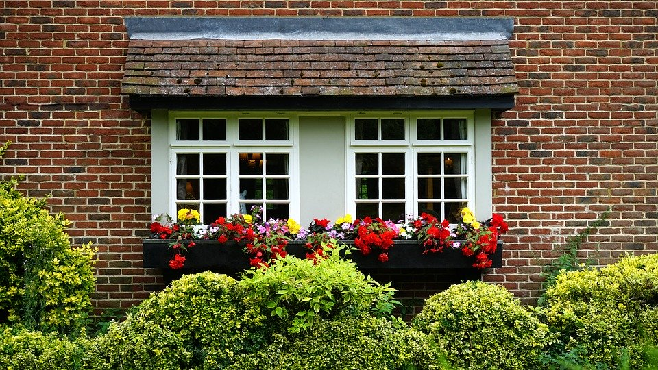 white windows on a brick house with flowers on the bottom.